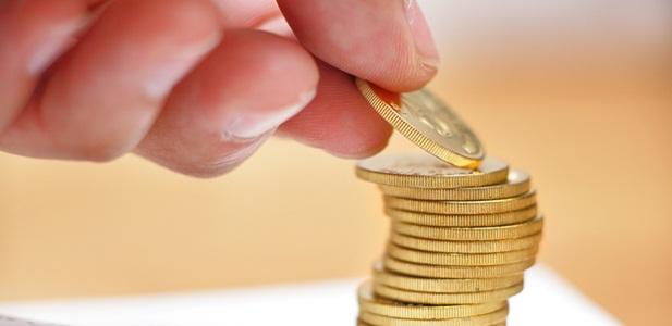 mão empilhando moedas