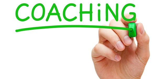 mão escrevendo coaching na tela