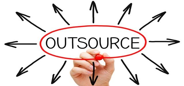 """mão escrevendo """"outsource"""" na tela"""