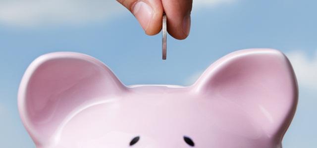 mão colocando moeda em cofre