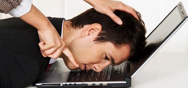 mãos empurrando cabeça de funcionário contra computador