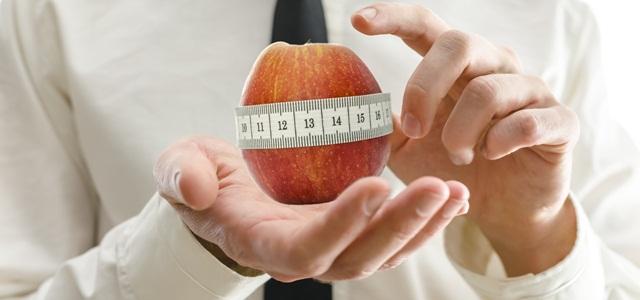 homem segurando maçã com fita métrica