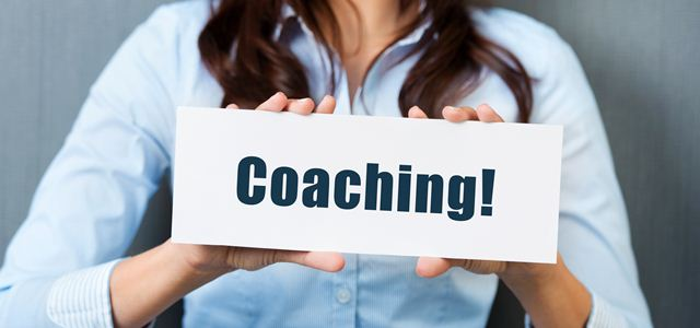"""mulher segurando placa com a palavra """"coaching"""""""