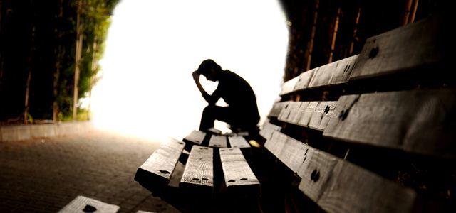 pessoa deprimida sentada em banco