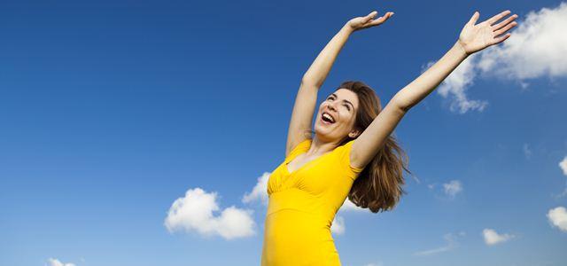 mulher sorrindo com os braços pra cima