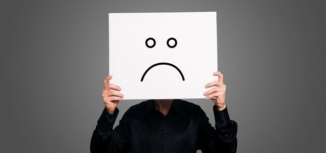 pessoa segurando cartaz com rosto triste