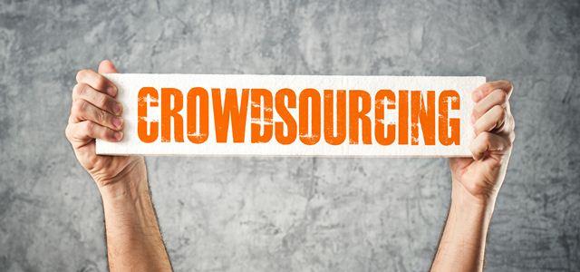 mãos segurando placa com a palavra crowdsourcing