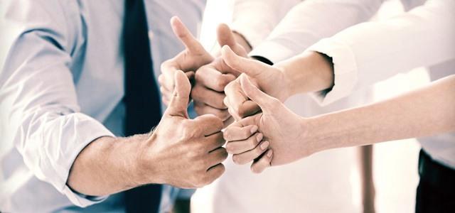 equipe com as mãos unidas e fazendo sinal de positivo