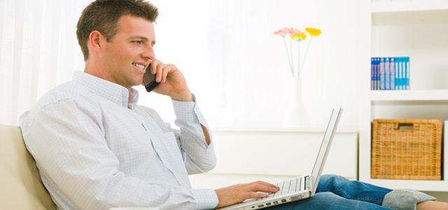 homem no sofá trabalhando e falando ao telefone