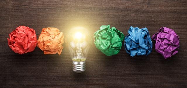 lâmpada acesa no meio de papeis amassados e coloridos