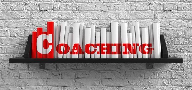 estante de livros com a palavra coaching