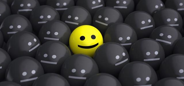 rosto feliz no meio de vários rostos tristes