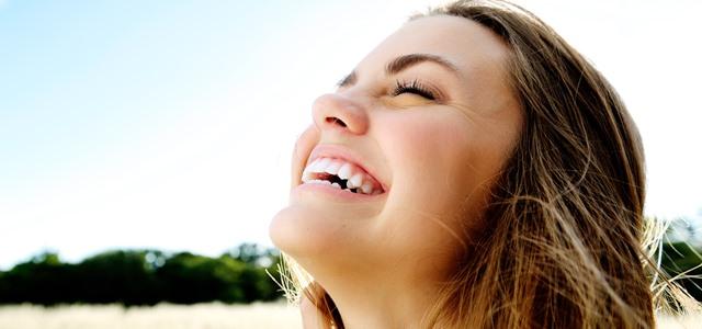 Jovem mulher sorrindo muito feliz, mostrando como sorrir faz bem, é bom