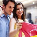 Casal, de homem e mulher, fazendo compras e carregando muitas sacolas