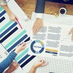 Profissionais avaliando diversos gráficos expostos sobre uma mesa