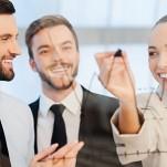 Profissionais olhando para quadro, onde mulher aponta, com um pincel, para um gráfico com número de vendas