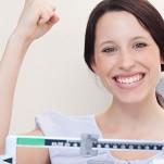 Mulher em cima da balança feliz pelo resultado positivo