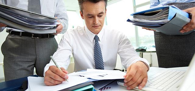 Profissional atolado pelo excesso de trabalho e recebendo mais demandas