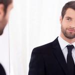 Homem se olhando no espelho observando sua autoimagem
