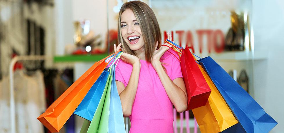 Mulher com compras mostrando que precisa aprender como desapegar das coisas