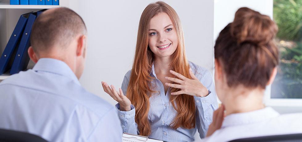 Profissional do sexo feminino durante entrevista comportamental com dois selecionadores