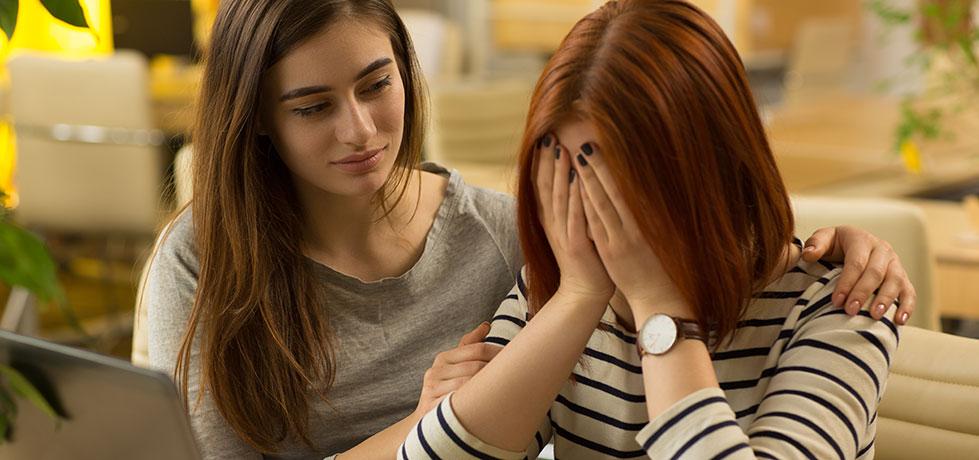 Colega ajudando uma pessoa emotiva no trabalho que chora