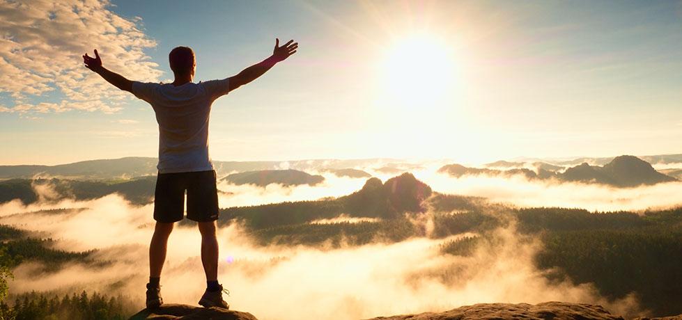 Filho feliz no topo da montanha