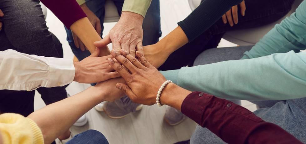 Grupo de pessoas juntando suas mãos