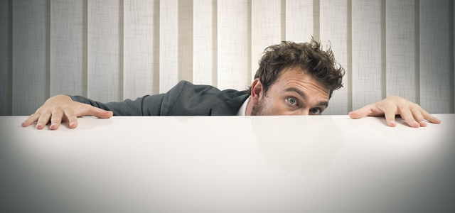 homem se escondendo atrás de mesa