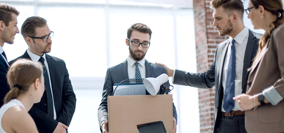 funcionário demitido sendo consolado por gestor e colegas