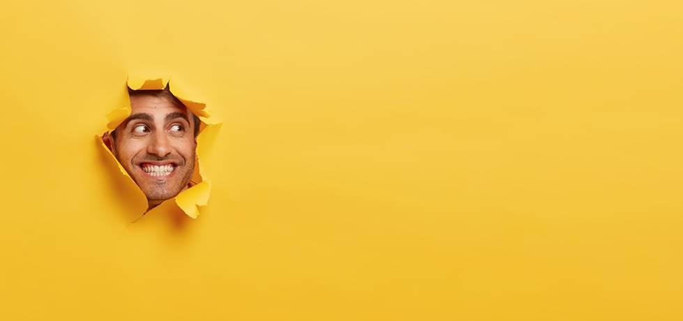 rosto de homem feliz atravessando uma parede de papel