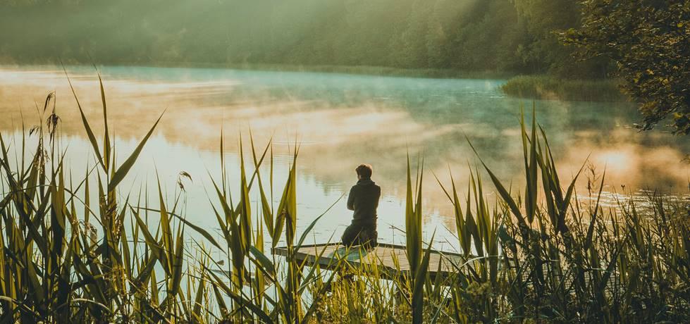 homem meditando a beira do lago