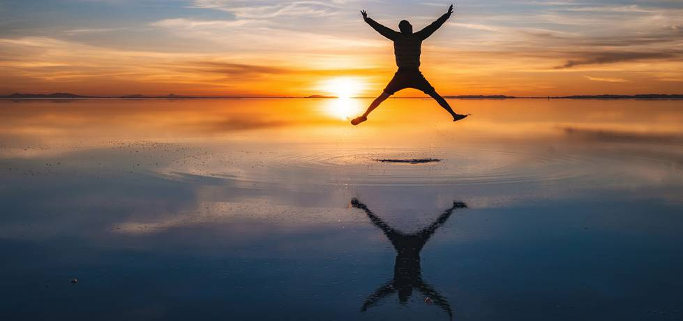homem saltando e observando o por do sol em uma praia