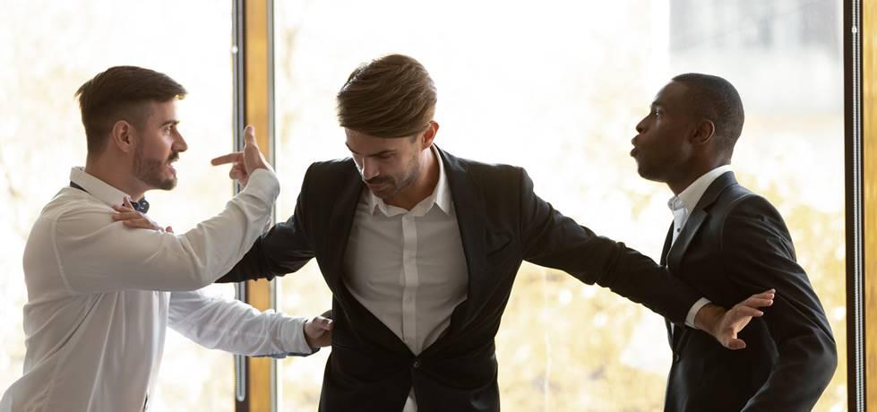 profissional segurando dois colegas de trabalho que estão brigando entre si