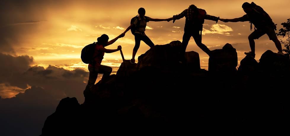 amigos ajundando uns aos outros a escalar uma montanha