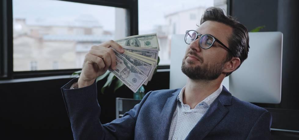 profissional se abanando com um maço de dinheiro