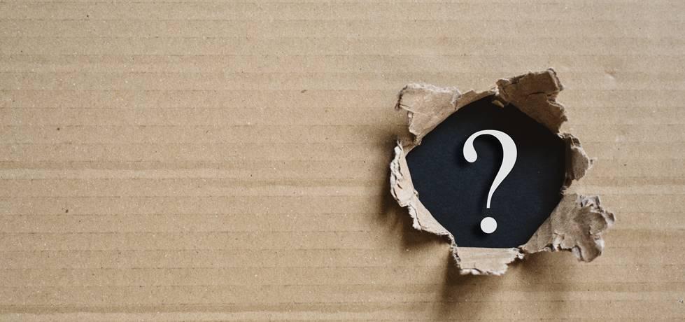 Caixa de papelão rasgada revelando ponto de interrogação