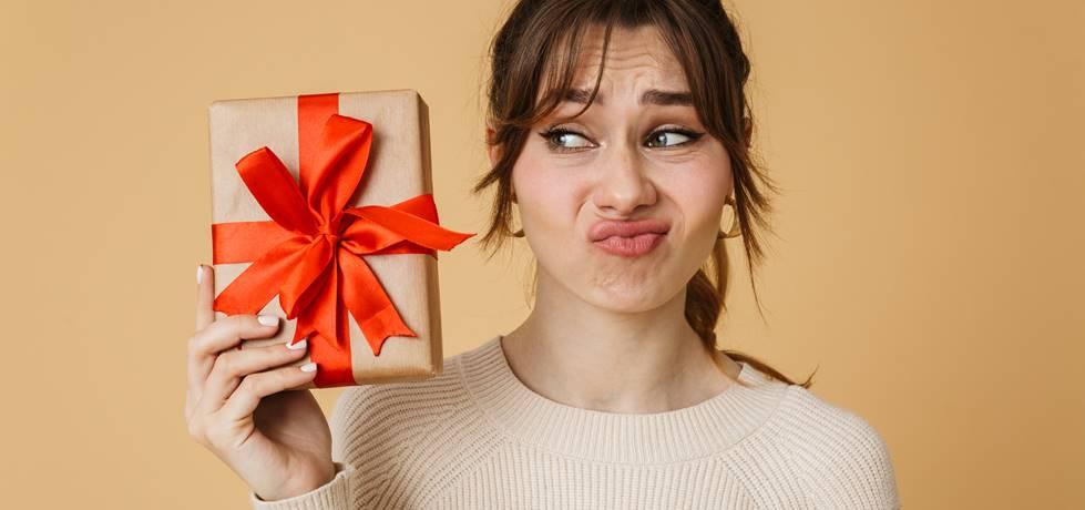 Mulher fazendo uma cara de insatisfeita enquanto segura um presente