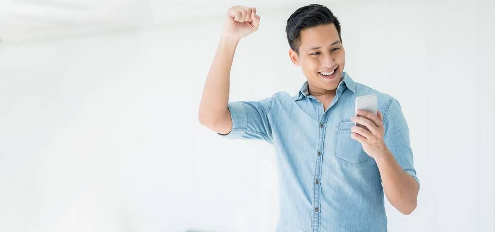Homem animado olhando para seu celular e levantando o braço para celebrar o sucesso.