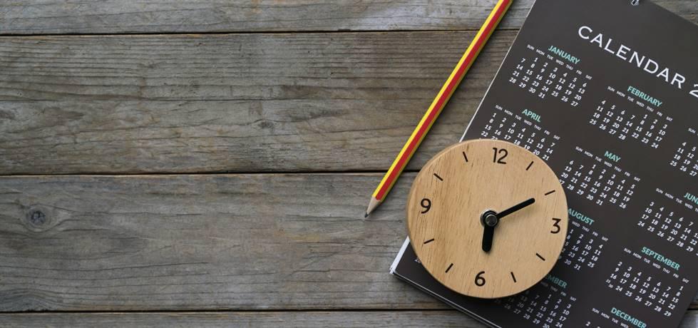 Relógio, calendário e lápis sobre a mesa.