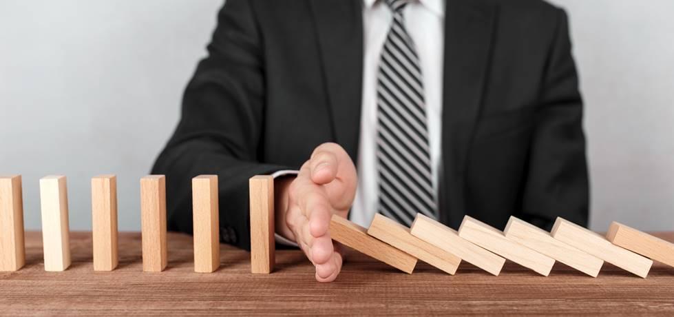 Vista da mão de um Homem de negócios parando blocos que estão caindo na mesa