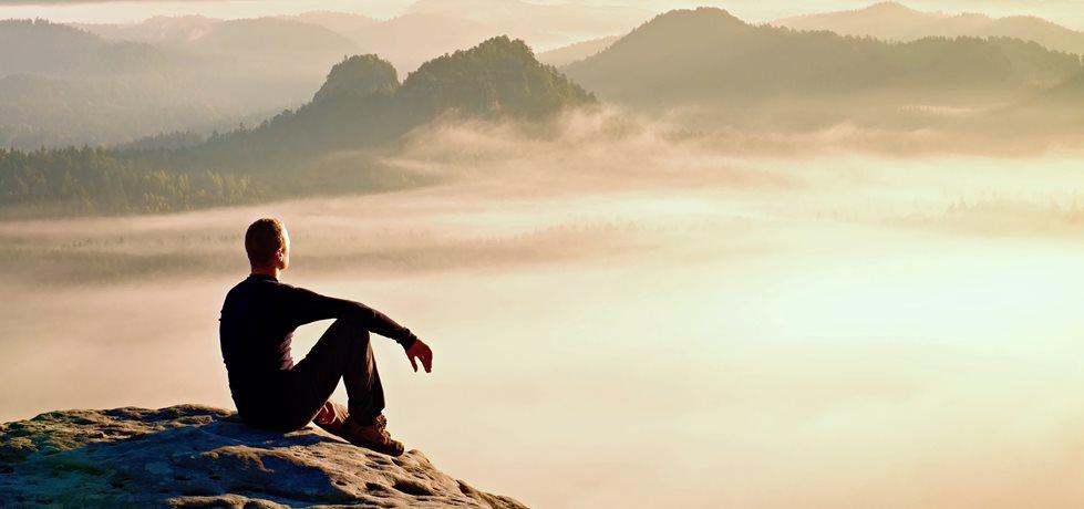 Homem sentado na montanha